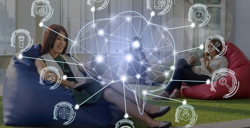 Polygonal brain shape of an artificial intelligence with various icon of smart city Internet of Things Technology over group of people businesswoman using the device, AI and business IOT concept